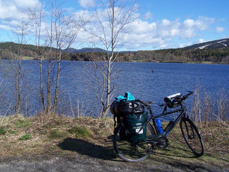 Reiserad mit Taschen vor See