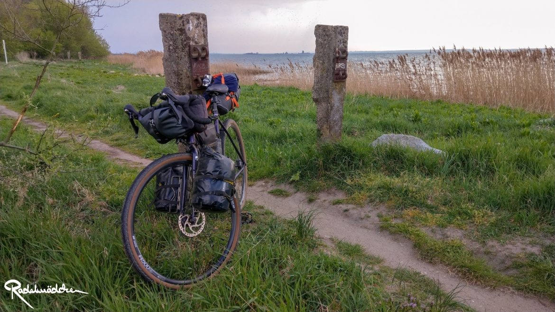 Gravelbike an Pfahl gelehnt mit Ostsee im Hintergrund