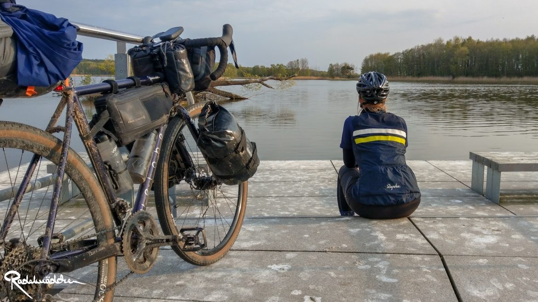 Radelmaedchen sitzt am Wasser mit Fahrrad im Vordergrund