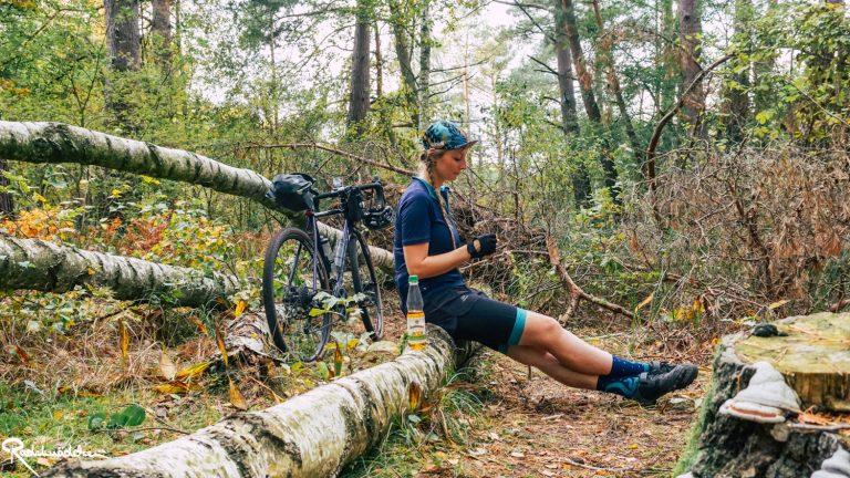 Radelmaedchen sitzt auf Baumstamm