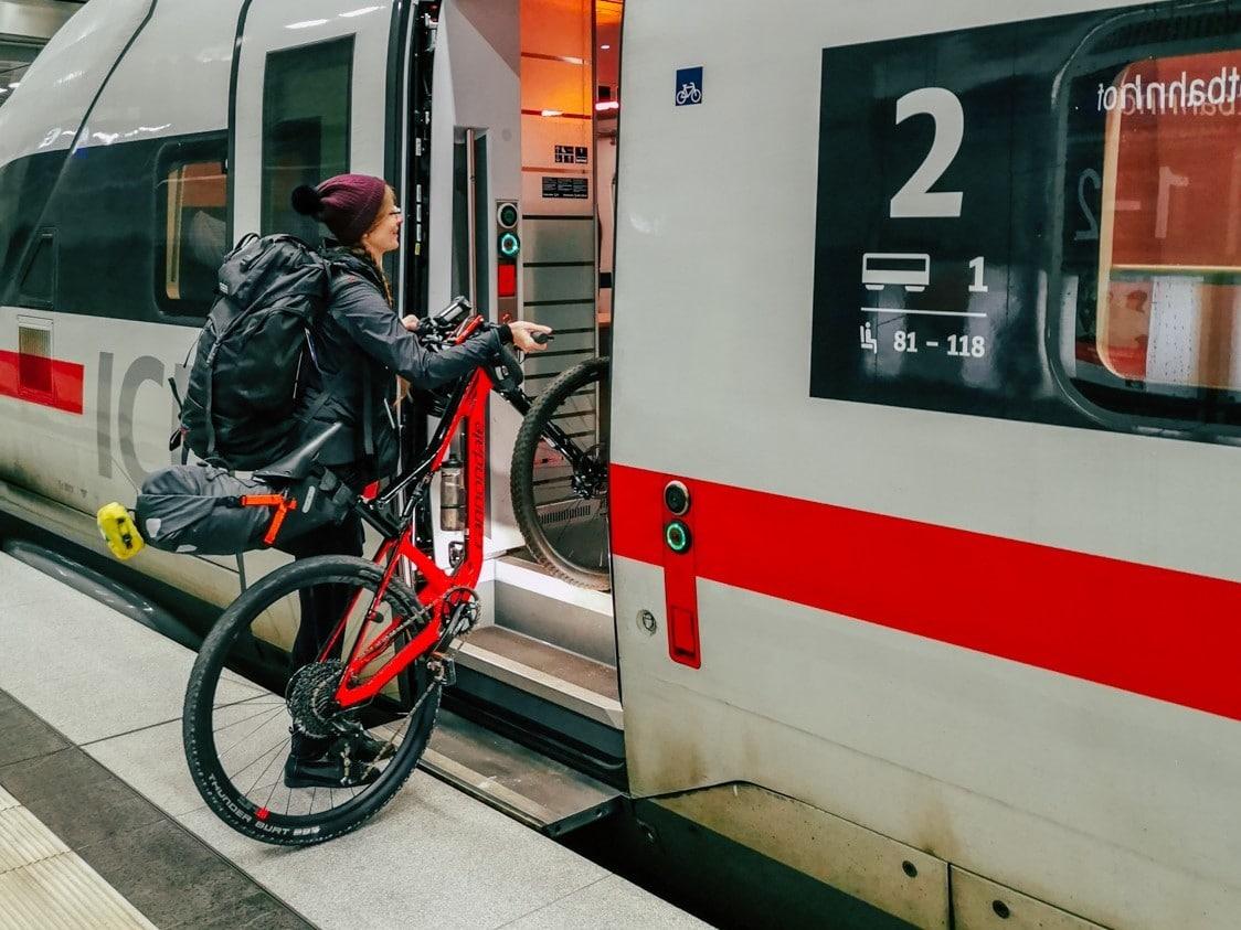 Radelmaedchen steigt mit Rad in den Zug