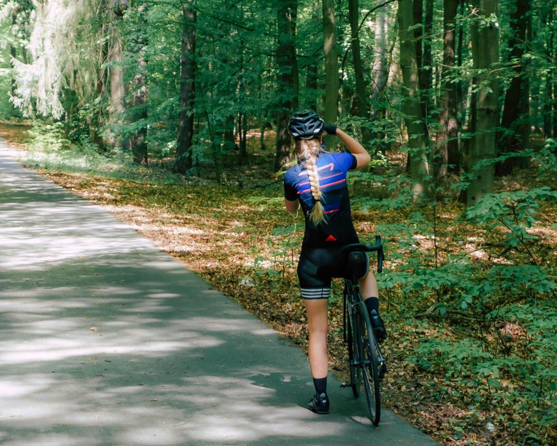 Radfahrerin macht Foto im Wald