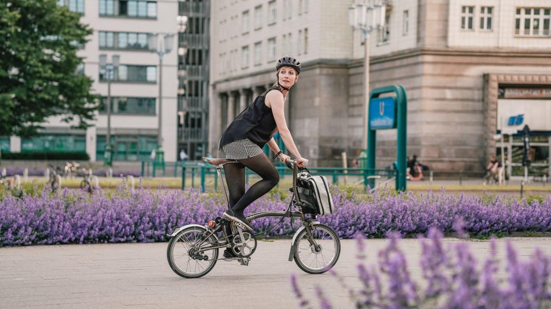 Brompton x FREITAG Rucksack am Faltrad mit Radfahrerin in der Stadt