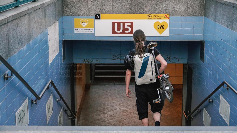 Mann geht mit dem Brompton auf der Schulter  in die U-Bahn