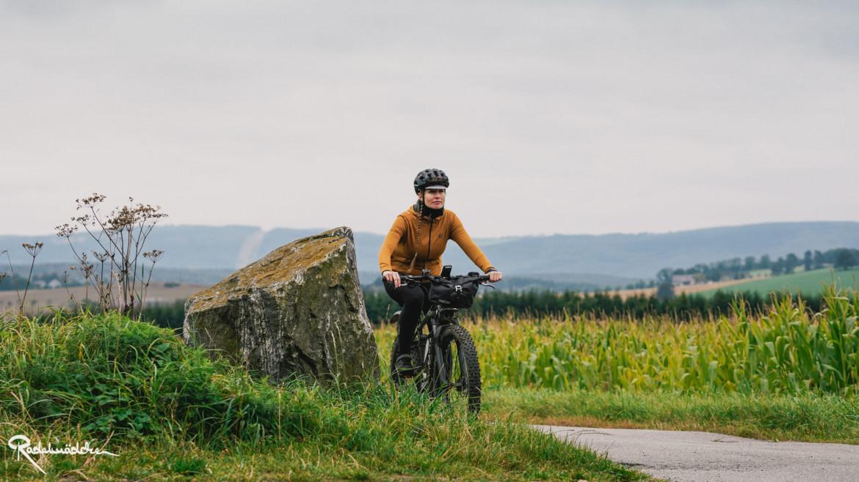 Frau auf dem Fahrrad vor einem Feld