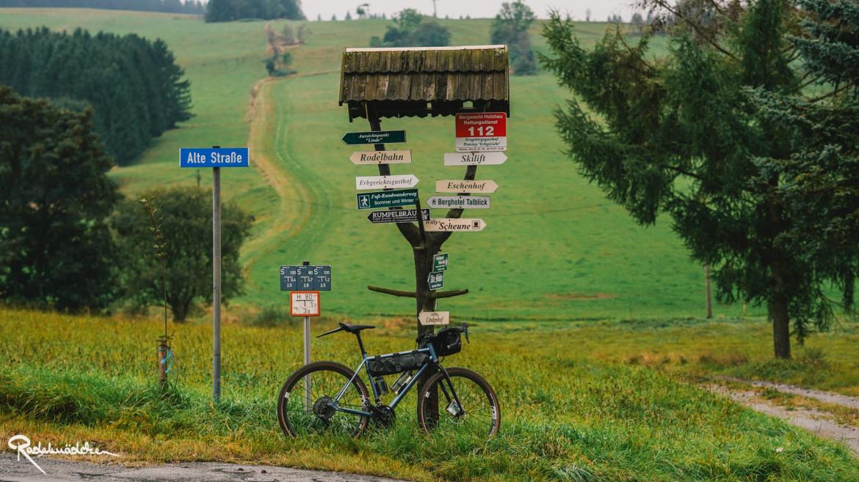 Fahrrad vor Schildern am Berg