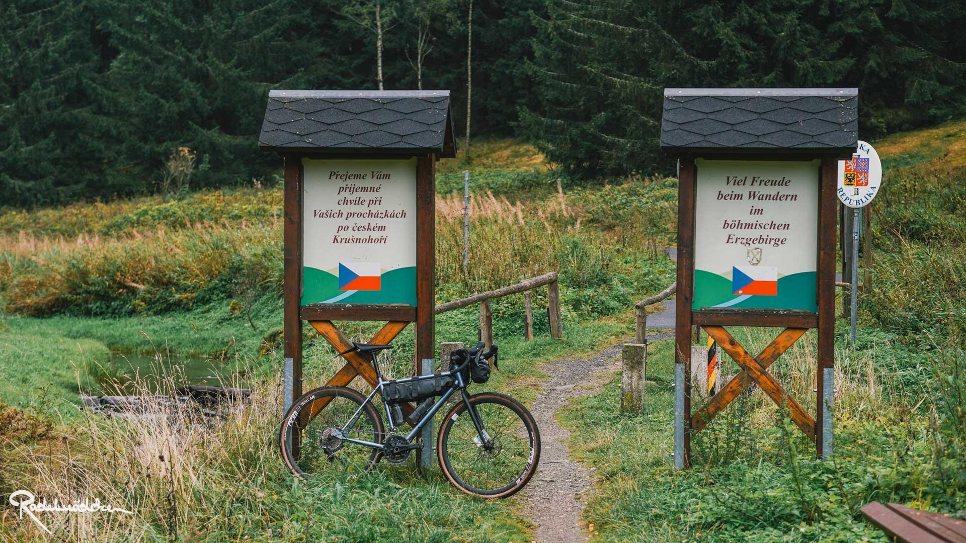 Schilder an der tschechischen Grenze im Grünen mit Fahrrad